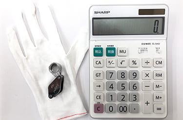 査定用白手袋とルーペと0が表示された電卓
