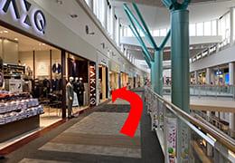 イオンモール伊丹3階TAKAQとその奥を左に指す矢印